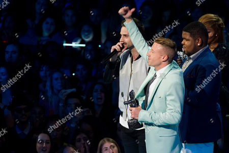 """Ryan Lewis, left, Macklemore, center, and Ray Dalton accept the award for best hip hop video for """"Can't Hold Us"""" at the MTV Video Music Awards, at the Barclays Center in the Brooklyn borough of New York"""