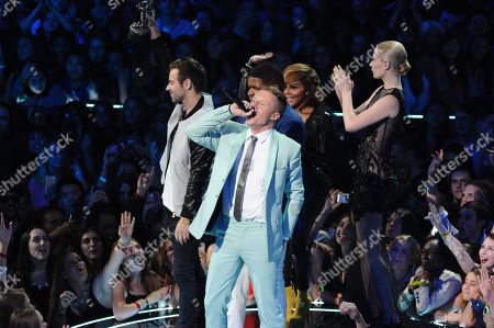 """Ryan Lewis, left, Macklemore, center, and Ray Dalton accept the award for best hip hop video for """"Can't Hold Us"""" as presenters Iggy Azalea, right, and Lil' Kim look, at the MTV Video Music Awards, at the Barclays Center in the Brooklyn borough of New York"""
