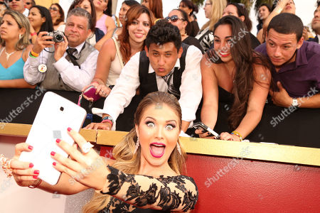 Kimberly Dos Ramos poses with fans during the 2014 Billboard Latin Music Awards on at the BankUnited Center in Coral Gables, Fla