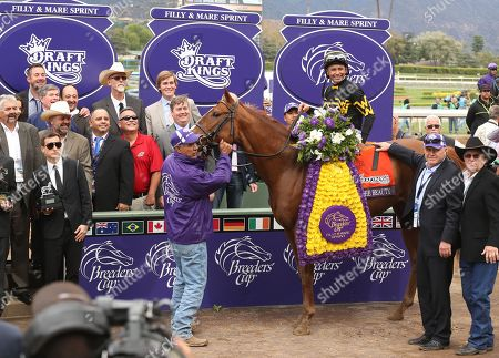 Stock Photo of Rob Dyrdek, left, presents the Filly and Mare Sprint trophy at day 2 of the 2014 Breeders' Cup World Championships at Santa Anita Park, in Arcadia, Calif