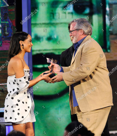 """Sean Bobbitt accepts the award for best cinematography from Zoe Kravitz, left, for """"12 Years a Slave"""" on stage at the 2014 Film Independent Spirit Awards,, in Santa Monica, Calif"""