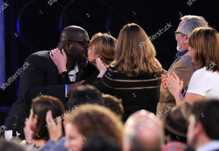 Steve McQueen, left, embraces Bianca Stigter in the audience after winning the best director award at the 2014 Film Independent Spirit Awards,, in Santa Monica, Calif