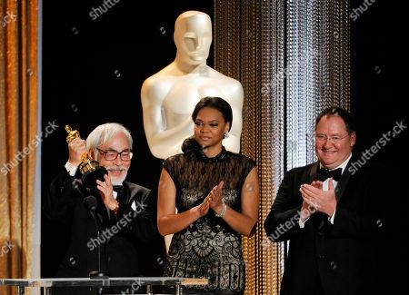 Japanese animator/director Hayao Miyazaki, left, accepts his Honorary Oscar as presenter John Lasseter, chief creative officer at Pixar, Walt Disney Animation Studios and DisneyToon Studios, looks on during the 2014 Governors Awards, in Los Angeles