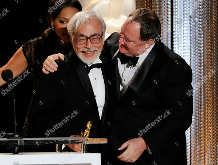 Japanese animator/director Hayao Miyazaki, left, is embraced by John Lasseter, chief creative officer at Pixar, Walt Disney Animation Studios and DisneyToon Studios, after receiving his Honorary Oscar during the 2014 Governors Awards, in Los Angeles