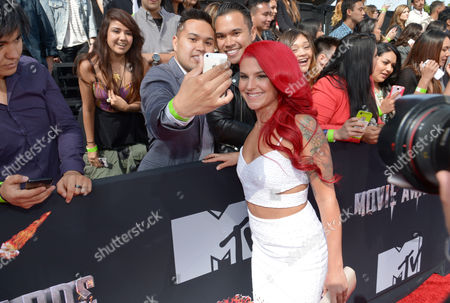 Carly Aquilino poses for a photo with a fan at the 2014 MTV Movie Awards, on in Los Angeles