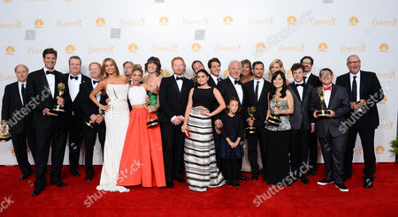 "Steve Levitan, and from left, Eric Stonestreet, Sofia Vergara, Sarah Hyland, Jesse Tyler Ferguson, Ariel Winter, Aubrey Anderson-Emmons, Julie Bowen, Nolan Gould, Rico Rodriguez, Ed O'Neill and the crew of ""Modern Family"" pose in the press room with the award for outstanding comedy series at the 66th Annual Primetime Emmy Awards at the Nokia Theatre L.A. Live, in Los Angeles"