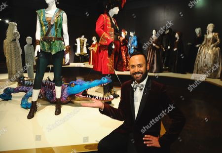 """Nick Verreos poses with costumes from """"Peter Pan Live!"""" seen at The 9th Annual Outstanding Art of Television Costume Design Exhibition opening at the FIDM Museum & Galleries on the Park, in Los Angeles. The Television Academy and FIDM Museum honored this year's Emmy(R) Award winners in Outstanding Costume Design at the opening reception for this annual special exhibition"""