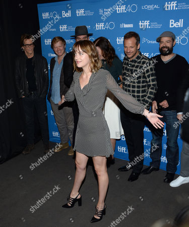 """Dakota Johnson attends a press conference for """"Black Mass"""" on day 5 of the Toronto International Film Festival at the TIFF Bell Lightbox, in Toronto. Pictured in background from left are Kevin Bacon, Jesse Plemons, Peter Sarsgaard and Rory Cochrane"""