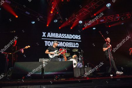 Tom Morello, center, performs with Noah Feldshuh, left, Adam Levin, on drums, and Sam Harris of X Ambassadors at the 2016 KROQ Almost Acoustic Christmas at The Forum, in Inglewood, Calif