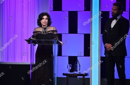 Sue Kroll accepts the Sid Grauman award at the 30th annual American Cinematheque Award at the Beverly Hilton Hotel, in Beverly Hills, Calif. Looking on at right is presenter Bradley Cooper