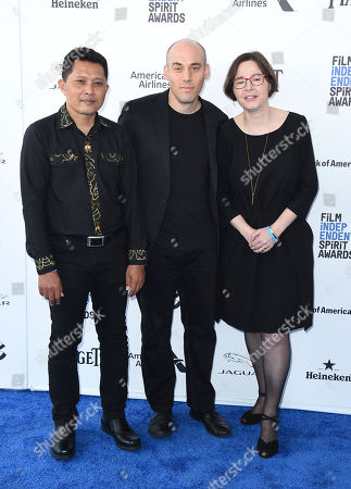 Adi Rukun, from left, Joshua Oppenheimer, and Signe Byrge Sorensen arrive at the Film Independent Spirit Awards, in Santa Monica, Calif