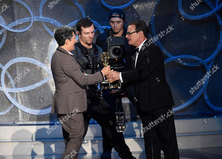 Peter Scolari, right, presents the award for outstanding directing for a comedy series to Jill Soloway for Transparent at the 68th Primetime Emmy Awards, at the Microsoft Theater in Los Angeles