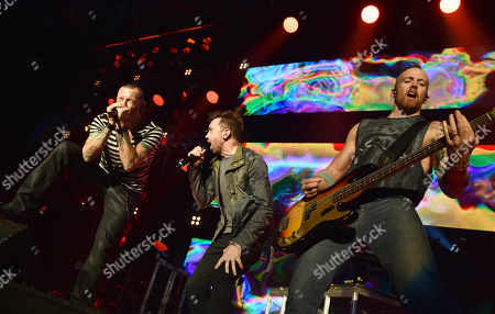 Tim McIlrath, of Rise Against, center, and from left, Chester Bennington and Dave Farrell, of Linkin Park, perform at the 25th annual KROQ Almost Acoustic Christmas at The Forum, in Inglewood, Calif
