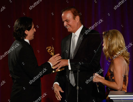 "NORTH HOLLYWOOD, CA - AUGUST 11: KMEX's Videographer Arturo Quezada (L) accepts the ""Outstanding Videographer - News"" award from reporter David Goldstein (C) and Dorothy Lucey onstage at the Academy of Television Arts & Sciences 64th Los Angeles Area Emmy Awards on in Los Angeles, California"