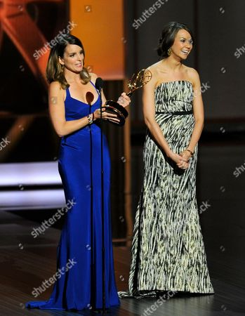 """From left, Tina Fey and Tracey Wigfield accept the award for outstanding writing for a comedy series for the work on """"30 Rock"""" at the 65th Primetime Emmy Awards at Nokia Theatre, in Los Angeles"""