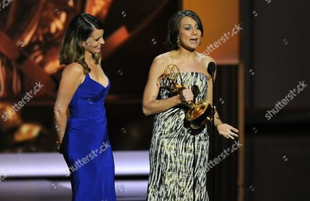 Tina Fey, left, and Tracey Wigfield accept the award for outstanding writing for a comedy series for their work on 30 Rock at the 65th Primetime Emmy Awards at Nokia Theatre, in Los Angeles