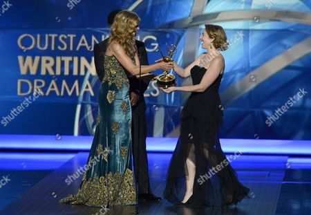 Connie Britton, left, presents the award for outstanding writing for a drama series to Sarah Bromell on behalf of Henry Bromell at the 65th Primetime Emmy Awards at Nokia Theatre, in Los Angeles