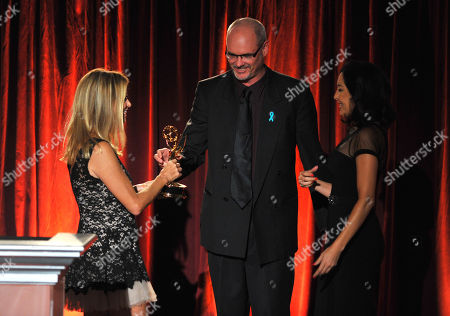 "Beatriz Gomez, Executive Producer of the KMEX news team, right, accepts the award for live special events-programming for ""Fiestas Patrias"" from Dorothy Lucey and David Goldstein at the Television Academy's 66th Los Angeles Area Emmy Awards on at The Leonard H. Goldenson Theater in the NoHo Arts District in Los Angeles"