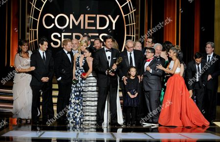 """Steven Levitan, center, and the producers and cast of """"Modern Family"""" accept the award for outstanding comedy series at the 66th Primetime Emmy Awards at the Nokia Theatre L.A. Live, in Los Angeles"""