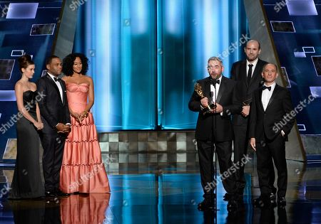 Simon Blackwell, from left, Tony Roche, and Amando Ianucci accept the award for outstanding writing for a comedy series for Veep Election Night at the 67th Primetime Emmy Awards, at the Microsoft Theater in Los Angeles. From left Anthony Anderson, and Tracee Ellis Ross look on