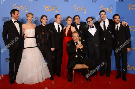 "From left, Bradley Cooper, Jennifer Lawrence, Megan Ellison, Eric Singer, Amy Adams, Charles Roven, David O. Russell, Eric Singer, Jonathan Gordon, and Matthew Budman pose in the press room with the award for best motion picture - comedy or musical for ""American Hustle"" at the 71st annual Golden Globe Awards at the Beverly Hilton Hotel, in Beverly Hills, Calif"