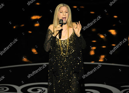 """Stock Photo of Actress/singer Barbra Streisand performs """"The Way We Were"""" for the In Memoriam tribute during the Oscars at the Dolby Theatre, in Los Angeles. Pictured on the screen is the song's Oscar-winning composer, Marvin Hamlisch, who died in 2012"""