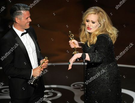 "Singer Adele, right, and musician/producer Paul Epworth accept the award for best music - original song for ""Skyfall"" from ""Skyfall"" during the Oscars at the Dolby Theatre, in Los Angeles"