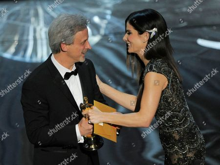 """Actress Sandra Bullock, right, presents the award for best film editing to William Goldenberg for """"Argo"""" during the Oscars at the Dolby Theatre, in Los Angeles"""
