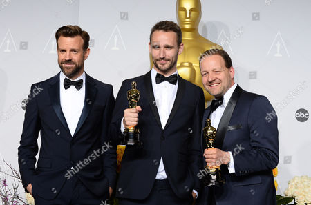 """Presenter Jason Sudeikis, left, poses with Anders Walter, and Kim Magnusson, right, in the press room with their award for best live action short film of the year for """"Helium"""" during the Oscars at the Dolby Theatre, in Los Angeles"""
