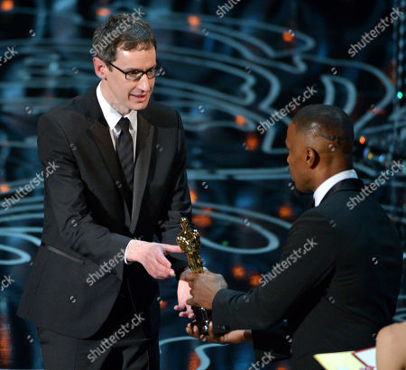 "Jamie Foxx, right, presents Steven Price with the award for original score in a feature film for ""Gravity"" during the Oscars at the Dolby Theatre, in Los Angeles"
