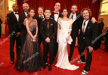 Actors Scott Adsit, from left, Damon Wayans Jr., Jamie Chung, Don Hall, Ryan Potter, Roy Conli, Genesis Rodriguez, Chris Williams, and T.J. Miller arrive at the Oscars, at the Dolby Theatre in Los Angeles