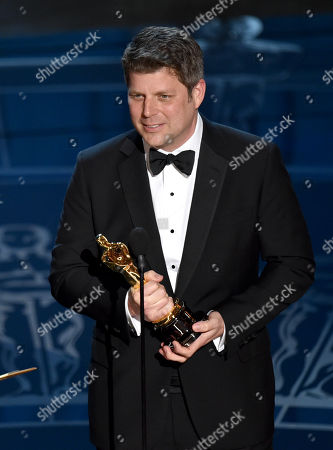 Adam Stockhausen accepts the award for best production design for The Grand Budapest Hotel at the Oscars, at the Dolby Theatre in Los Angeles
