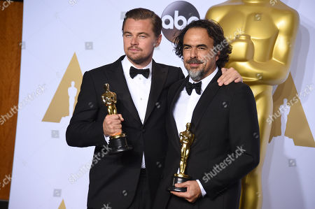 Leonardo DiCaprio, winner of the award for best actor in a leading role for The Revenant, left, and Alejandro G. Inarritu, winner of the award for best director for The Revenant, pose in the press room with their awards at the Oscars, at the Dolby Theatre in Los Angeles