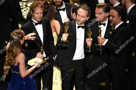 Laszlo Nemes looks on as Brie Larson, left, take a photograph of Emmanuel Lubezki, Leonardo DiCaprio, and Alejandro G. Inarritu on stage at the conclusion of the show at the Oscars, at the Dolby Theatre in Los Angeles