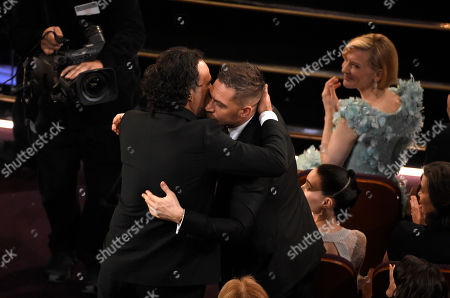 Alejandro G. Inarritu, left, hugs Tom Hardy in the audience after winning the award for best director for The Revenant at the Oscars, at the Dolby Theatre in Los Angeles