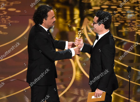 J.J. Abrams, right, presents Alejandro G. Inarritu with the award for best director for The Revenant at the Oscars, at the Dolby Theatre in Los Angeles