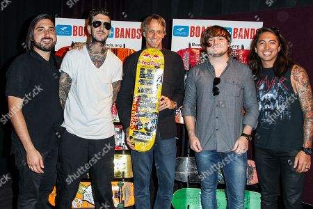 Skateboarder Tony Hawk, center, poses with members of the group Of Mice & Men, from left, Valentino Arteaga, Austin Carlile, Aaron Pauley, and Phil Manansala attend the Boards and Bands Auction press conference held at The London West Hollywood on in West Hollywood, Calif