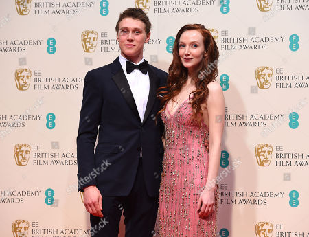 George McKay, left, and Olivia Grant pose for photographers in the winners room, during the British Academy Film and Television Awards 2015, at the Royal Opera House, in London