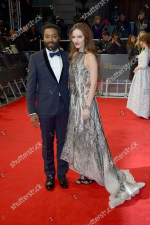 Chiwetel Ejiofor and and Shari Mercer pose for photographers on the red carpet at the EE British Academy Film Awards held at the Royal Opera House, in London