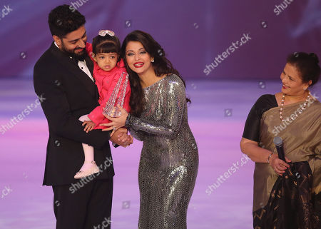 Former Miss World Aishwarya Rai, centre speaks on stage with husband Abhishek Bachchan and daughter Aaradhya Bachchan, during the Miss World 2014 final, on stage at the Excel centre in east London