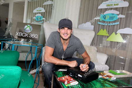 Rick Malambri signs an Xbox at the Xbox 360 and Children's Miracle Network Gaming and Giving for Good (G3) Miracle Lounge on in West Hollywood, Calif