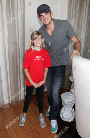Rick Malambri, right, poses with CHOC patient Katie Gerberding, 10, at the Xbox 360 and Children's Miracle Network Gaming and Giving for Good (G3) Miracle Lounge on in West Hollywood, Calif