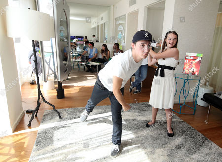 Mitchel Musso, left, plays games with CHLA patient Eileen Garrido, 13, at the Xbox 360 and Children's Miracle Network Gaming and Giving for Good (G3) Miracle Lounge on in West Hollywood, Calif