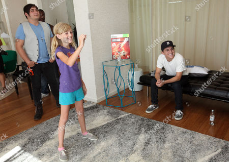 Mitchel Musso, right, plays a game with CHOC patient Katie Gerberding, 10, center, and his brother Mason Musso at the Xbox 360 and Children's Miracle Network Gaming and Giving for Good (G3) Miracle Lounge on in West Hollywood, Calif