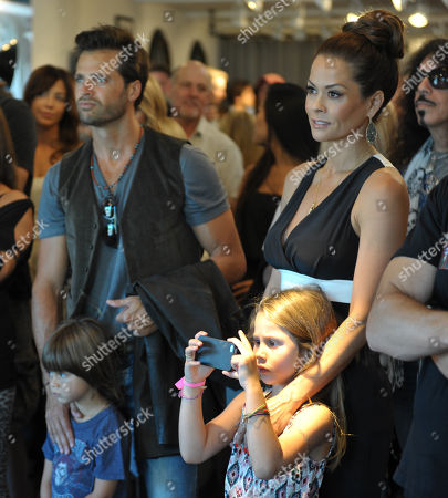 Brooke Burke Charvet, right, and husband David Charvet watch a Glenn Hughes performance with their son Shaya, bottom left, and daughter Heaven Rain at a John Varvatos private event, in Malibu, Calif