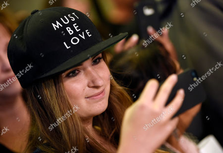 """Lauren Moeller of Thousand Oaks, Calif., a fan of the late singer and """"The Matchbreaker"""" cast member Christina Grimmie, wears a hat referencing Grimmie's debut single at the premiere of the film at the ArcLight Cinerama Dome, in Los Angeles. Grimmie, a singer on the television singing competition series """"The Voice,"""" was shot and killed while signing autographs and meeting fans following a concert in June in Orlando, Fla"""