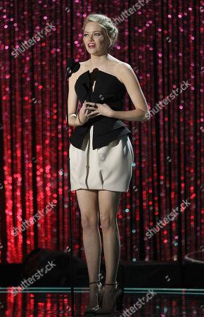 Emma Stone accepts the award the trailblazer award at the MTV Movie Awards on in Los Angeles. At left is presenter Martha MacIsaac