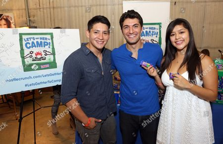 Stock Picture of Actor Carlos Pratts, left, supports the #LetsGetHerToCamp campaign with Nestle Crunch Girl Scout Candy Bars at a Teen Choice Awards gift suite on in Los Angeles. To help send girls to Girl Scout camp visit NestleCrunch.com/LetsGetHerToCamp by August 31