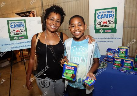 Actor Tylen Jacob Williams, right, and Angela Williams support the #LetsGetHerToCamp campaign with Nestl? Crunch Girl Scout Candy Bars at a Teen Choice Awards gift suite on in Los Angeles. To help send girls to Girl Scout camp visit NestleCrunch.com/LetsGetHerToCamp by August 31