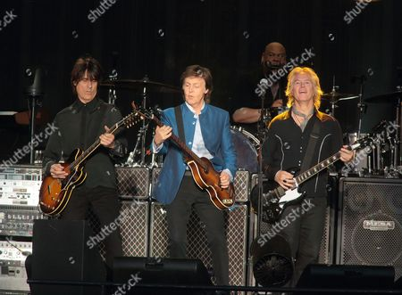 Stock Image of Rusty Anderson, from left, Paul McCartney and Brian Ray perform in concert at Hersheypark Stadium, in Hershey, Pa